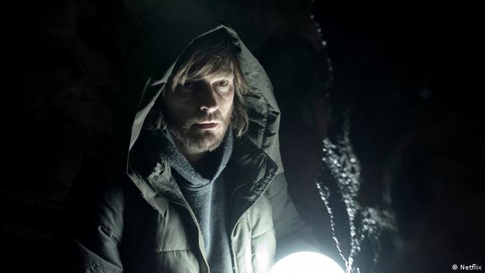 Personagem de Dark segura uma lanterna em uma caverna. Ele é um homem de cerca de 40 anos, de barba, e veste uma jaqueta com capuz.