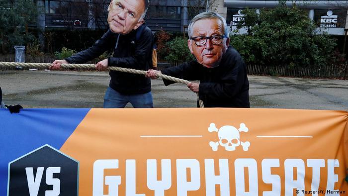 People wearing Juncker mask behind a banner saying democracy vs. glyphosate