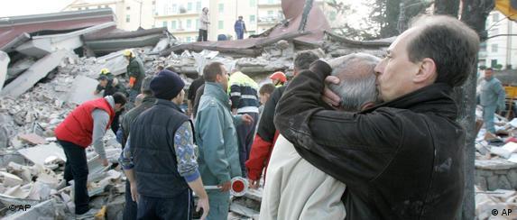 Menschen umarmen sich und stehen fassungslos vor den Trümmerbergen (Foto: AP)