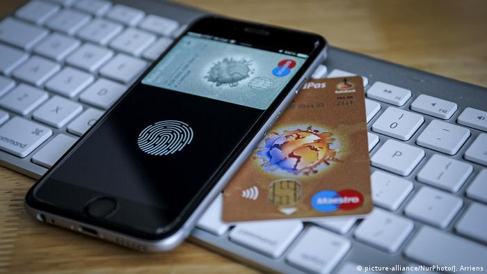 An Iphone and a maestro debit card on top of a Mac keyboard