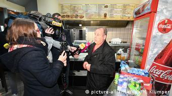 Pai de donos do quiosque de kebab é questionado por jornalistas no local onde o prefeito de Altena foi agredido
