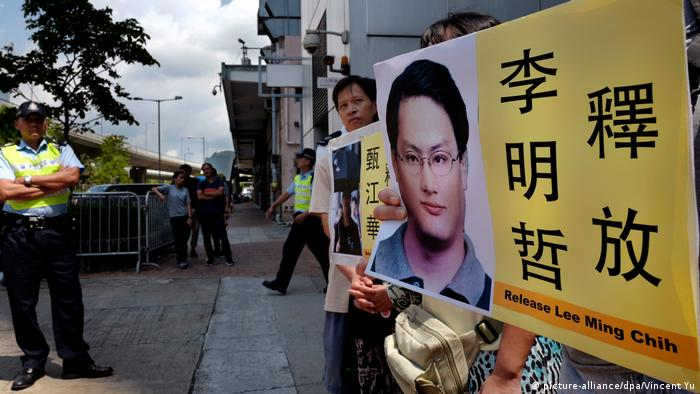 People demonstrate in Hong Kong with photos of the Taiwanese human rights activist Lee Ming-che