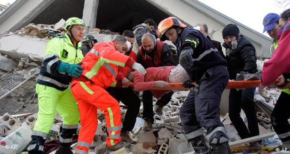 Firefighters remove an injured woman from the rubble of a collapsed building