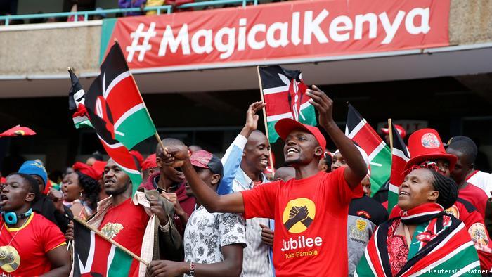 Supporters of President Uhuru Kenyatta at his inauguration waving Kenyan flags