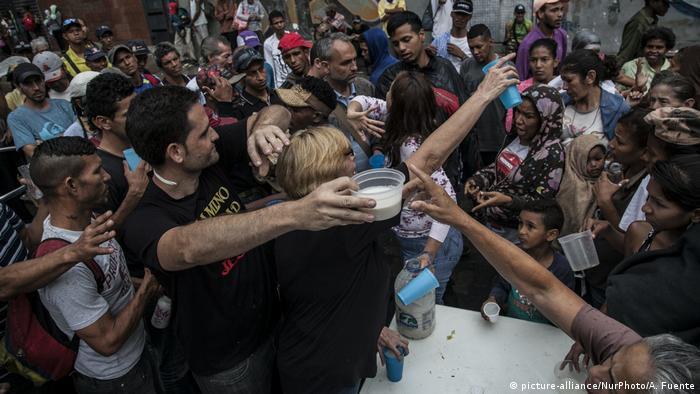 Mneschen drängen sich vor einer Lebensmittelausgabe in Caracas (picture-alliance/NurPhoto/A. Fuente)