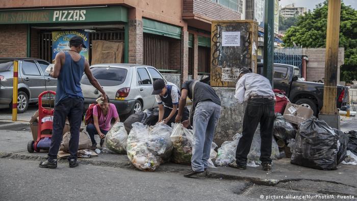 Personas en Caracas, Venezuela, buscan comida en bolsas de basura.