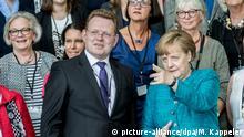 ARCHIV - Bundeskanzlerin Angela Merkel (CDU) steht am 17.05.2017 in Berlin bei der Verleihung des Nationalen Integrationspreises neben Andreas Hollstein, dem Bürgermeister der Stadt Altena (Nordrhein-Westfalen). Die Stadt mit ihrem Leitbild Vom Flüchtling zum Altenaer Mitbürger war Preisträgerin. (zu dpa Merkel: Bin entsetzt über Messerangriff auf Bürgermeister von Altena vom 28.11.2017) Foto: Michael Kappeler/dpa +++(c) dpa - Bildfunk+++   Verwendung weltweit