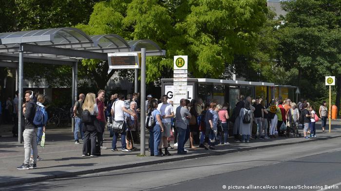 Parada de autobús llena de gente.