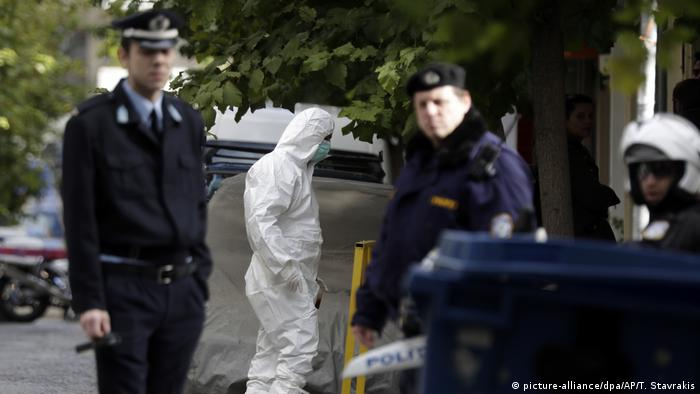 A man in hazmat suit enters an apartment in Athens (picture-alliance/dpa/AP/T. Stavrakis)