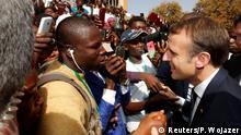 French President Emmanuel Macron shakes hands with people in the crowd as he leaves the Ouagadougou University, in Ouagadougou, Burkina Faso, November 28, 2017. REUTERS/Philippe Wojazer