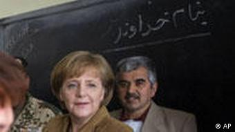 German Chancellor Angela Merkel (right) smiles during her visit to the Ali Chapan High School in Mazar-e-Sharif, Afghanistan