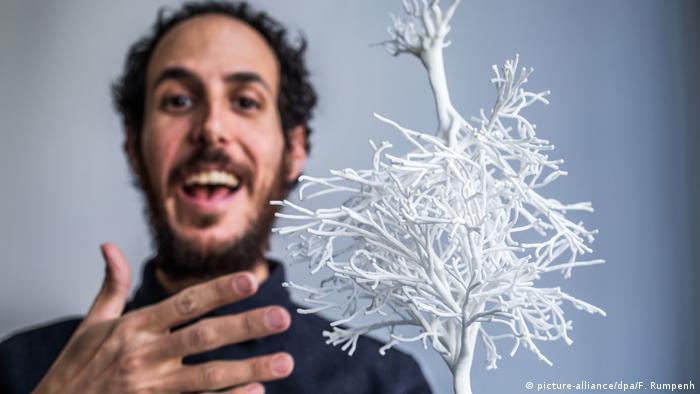 Der in Mexiko lebende israelische Künstler Ariel Schlesinger neben einem Modell seiner Außenskulptur für das neue Jüdische Museum in Frankfurt: zwei weiße miteinander verschränkte Bäume