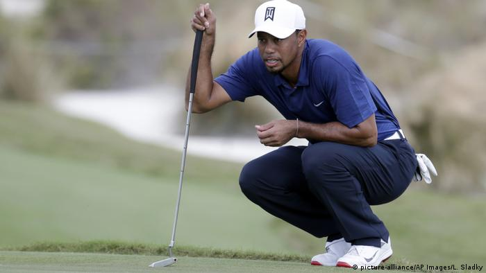 Golfprofi Tiger Woods studiert hockend das Gelände (Foto: picture-alliance/AP Images/L. Sladky)