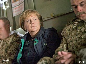 German Chancellor Angela Merkel, center, is seen sitting between German army Bundeswehr soldiers during her flight from Kunduz to Mazar-e-Sharif, Afghanistan, on Monday April 6, 2009