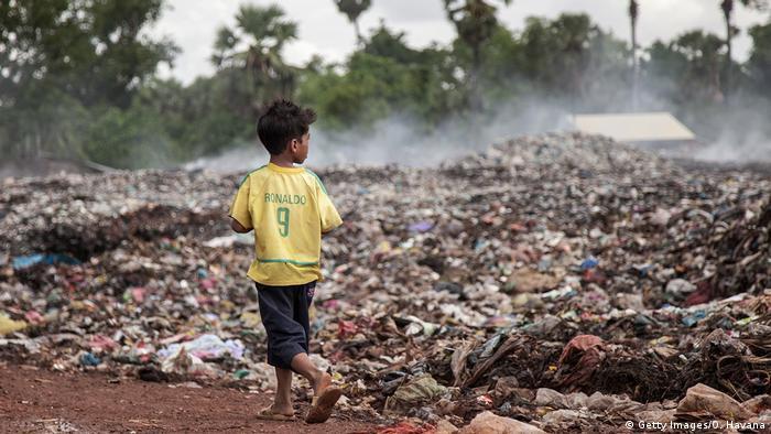 Criança com camiseta do Ronaldo caminha ao lado do lixo