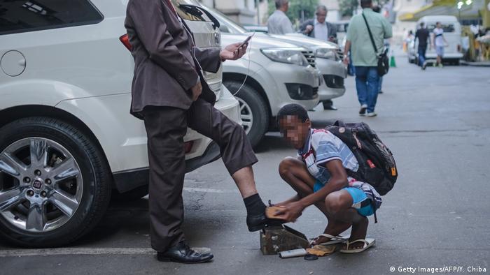 Cena do cotidiano: garoto engraxa os sapatos de um homem, que consulta o celular no Rio
