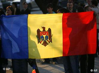 Anti-communist demonstrators hold the Moldovan flag outside the presidential palace Monday April 6, 2009 in Chisinau, Moldova.