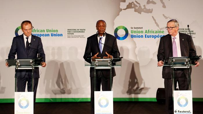 EU leaders Donald Tusk and Jean-Claude Juncker stand with President Alpha Conde of Guinea
