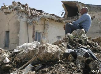 A man sits on rubbles in the Italian village of Onna