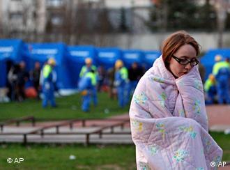 Frau vor Helfern und blauen Zelten (Quelle: AP)