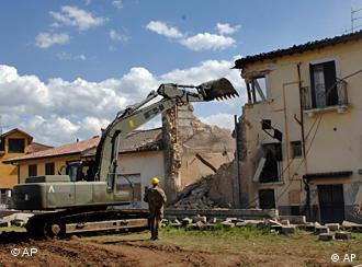 A front hoe tearing down a partially collapsed building near L'Aquila