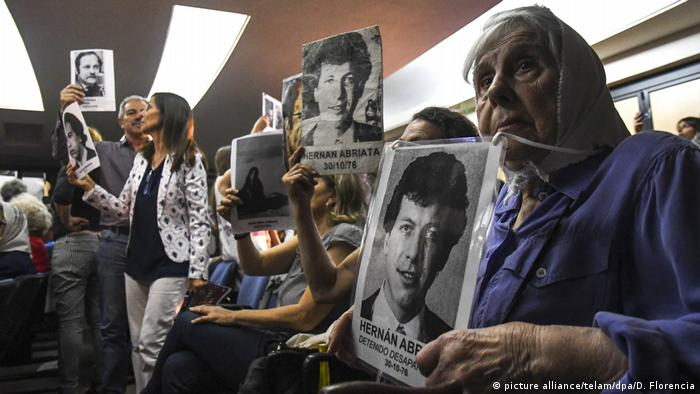 Activists hold pictures of victims of Argentina's dictatorship