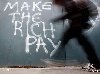 A man walks past graffiti in Dublin which reads Make the rich pay.