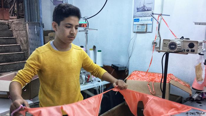 A young Syrian boy sorting through cotton fabric