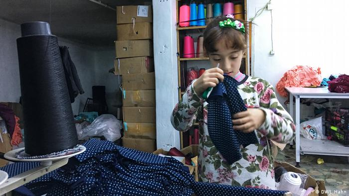 A young girl folding garments
