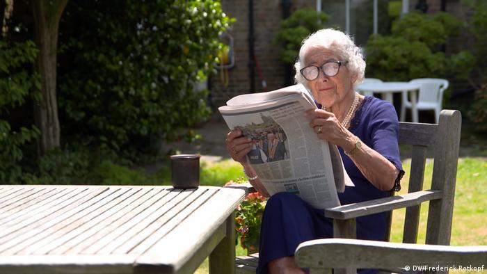 Die britische Schriftstellerin Judith Kerr sitzt 2017 in ihrem Garten in London und liest Zeitung (DW/Frederick Rotkopf)
