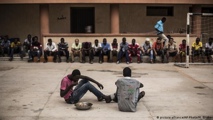 People sitting in a migrant detention center in Libya (picture-alliance/AP Photo/M. Brabo)