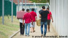 Migrants in Ingelheim, Germany, seen from behind with suitcases (picture-alliance/dpa/C. Schmidt)