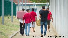 ARCHIV - Flüchtlinge laufen am 27.08.2015 mit Koffern bepackt auf einem Weg einer Erstaufnahmeeinrichtung für Flüchtlinge in Ingelheim (Rheinland-Pfalz) entlang. (zu dpa «Saar-Regierung beziffert Flüchtlingskosten» vom 12.11.2017) Foto: Christoph Schmidt/dpa +++(c) dpa - Bildfunk+++ | Verwendung weltweit