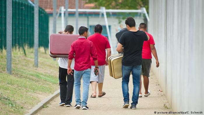 Migrants in Ingelheim, Germany, seen from behind with suitcases