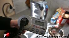 Ein Energieberater misst am 14.11.2012 in Aachen (Nordrhein-Westfalen) in der Wohnung von Remigiosz Partyka den Stromverbrauch des Wasserkochers. Strom ist teuer. Und er wird noch teurer. Menschen wie Remigiosz Partyka müssen sparen, damit sie ihre Rechnung bezahlen können. Aber gegen den Stromfresser Kühlschrank ist er machtlos. Foto: Oliver Berg/dpa (zu lnw-KORR: Jedes Watt zählt - Herr Partyka muss Strom sparen) +++(c) dpa - Bildfunk+++   Verwendung weltweit
