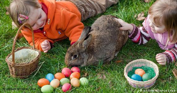 Kinder mit bunten Ostereiern und Kaninchen