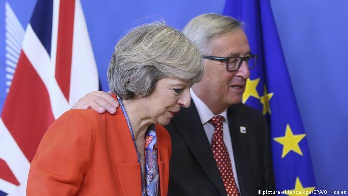 European Commission head Jean-Claude Juncker leads UK PM TheresaMay away