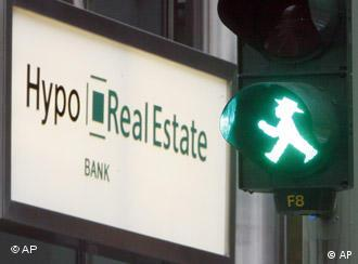 A green pedestrian traffic light next to a sign saying Hypo Real Estate