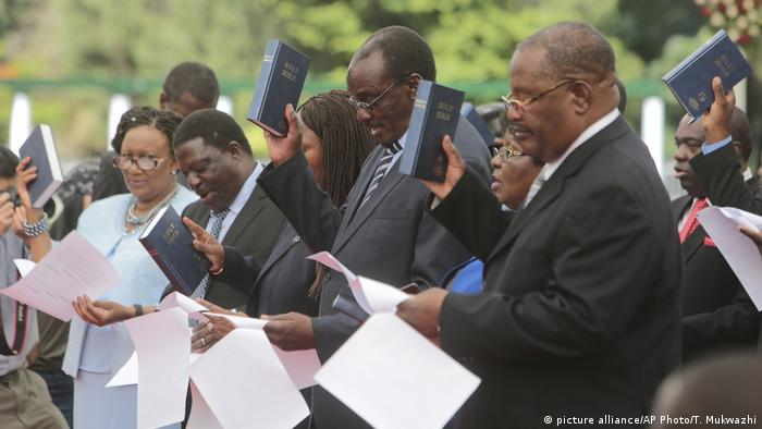 A group of ministers that make up Zimbabwe's new cabinet sworn in in December read their oaths of office – each holding documents in one hand and a bible held high in the other.