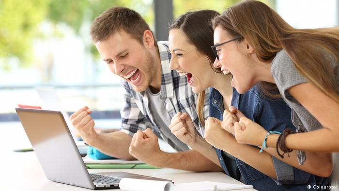 Three people laughing at a Laptop (Colourbox)