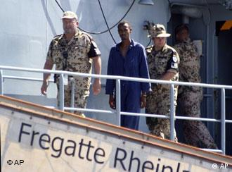 German military personnel escort one of seven suspected Somali pirates
