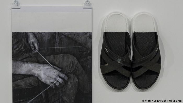 A black-and-white photo is hanging on a wall, right next to a pair of black sandals. (Victor Leguy/Sahir Uğur Eren)