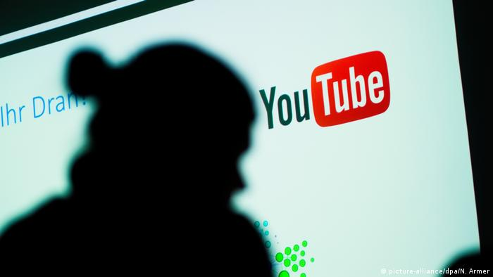 The silhouette of a woman next to the YouTube logo (picture-alliance/dpa/N. Armer)