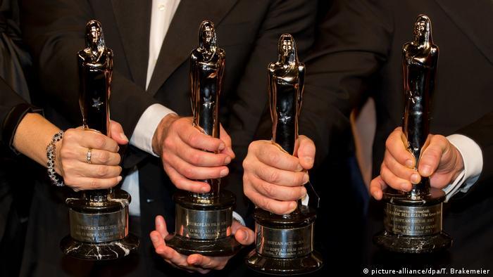 Hands hold four European Film Award statues