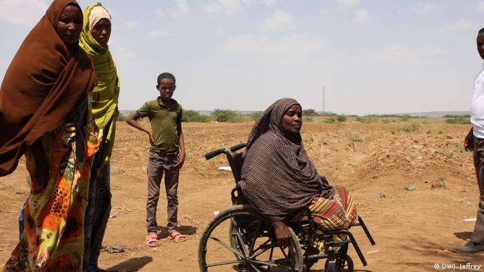 Somali woman in a wheelchair surrounded by other displaced Somali Ethiopians