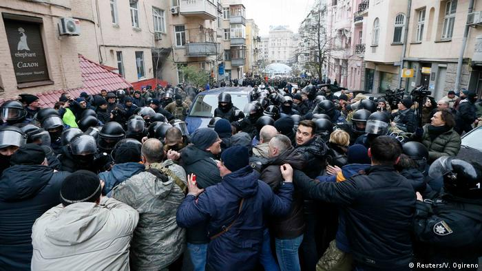 Protesters wrestle with the police around the police van in Kyiv (Reuters/V. Ogireno)