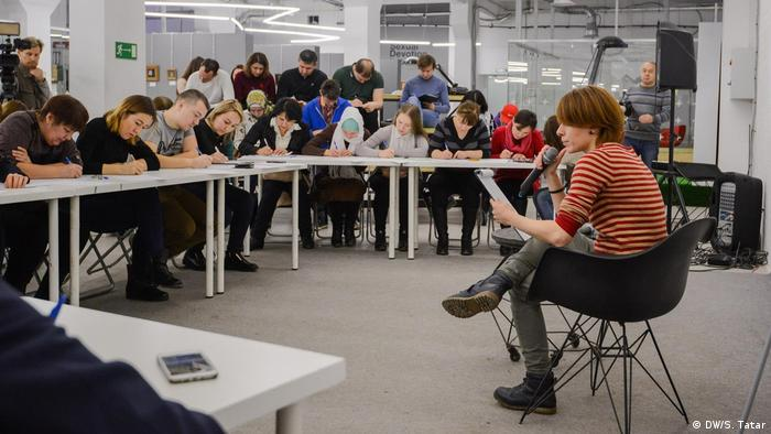 Participants write along to the dictation of Tatar literature at a mass dictation event in Kazan