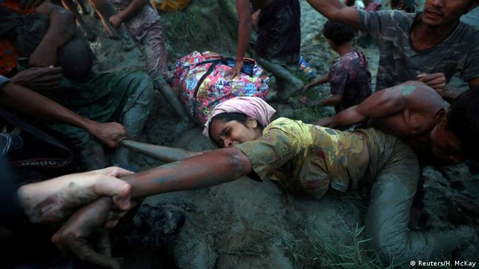 Helping a Rohingya refugee out of the Naf River at the border with Bangladesh
