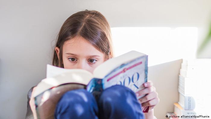 Djevojčica koncentrirano čita knjigu