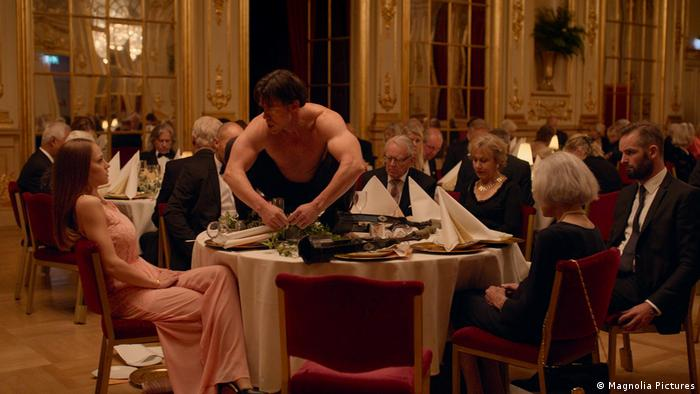 The Square Film scene with a dinner party, and a man performing as an ape (Magnolia Pictures)